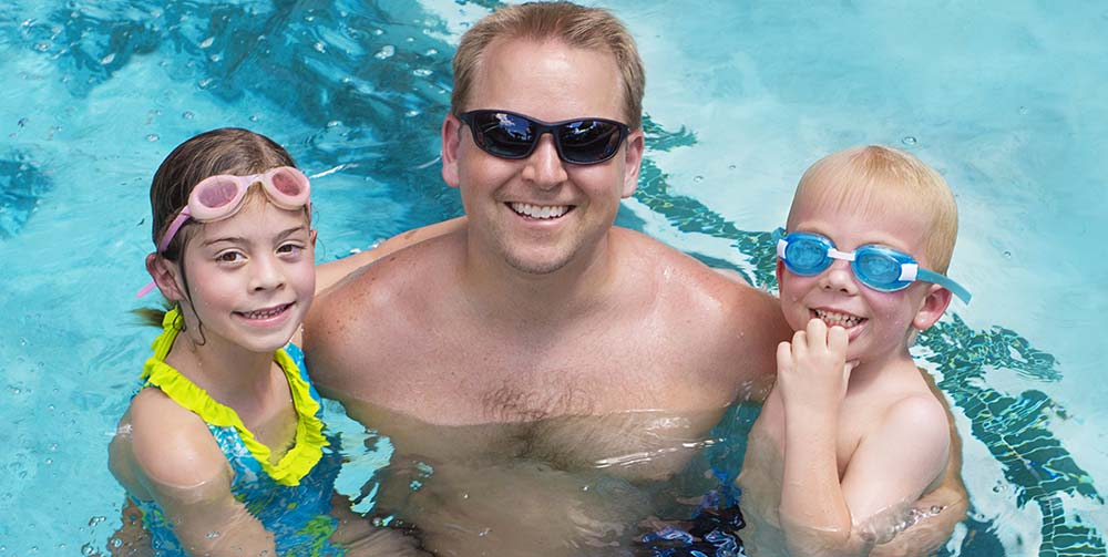 Family wearing sunglasses and goggles while swimming